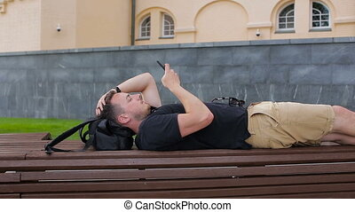 A young man uses a phone on a bench in the city