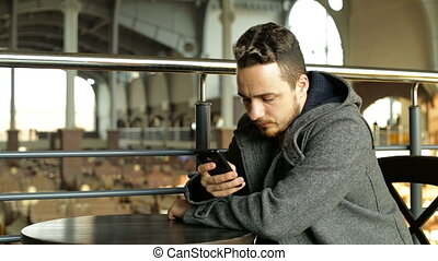 A young man uses the phone and drinking coffee in a cafe in a large shopping center