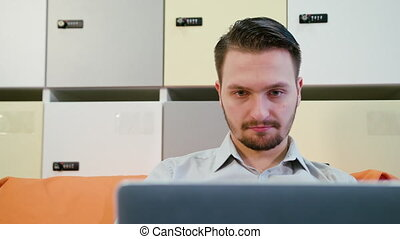 A Young Man Using a Laptop Indoors
