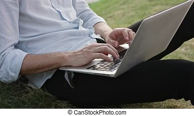 A Young Man Using a Laptop Outdoors