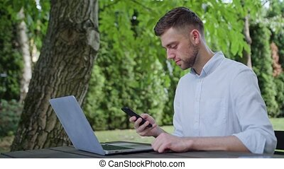 A Young Man Using a Phone in the Park