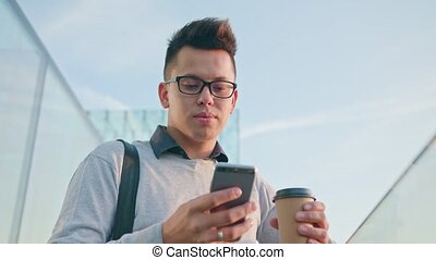 A Young Man Using a Phone Outside