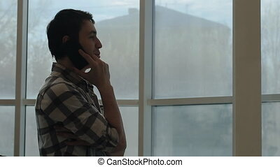 A young man using a smartphone to order food to your home by calling, in front of windows.
