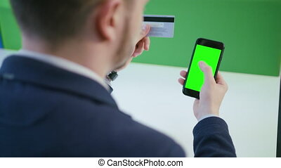 A Young Man Using a Smartphone with a Green Screen