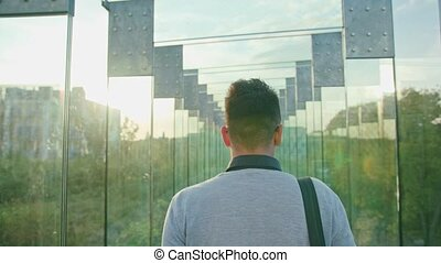 A Young Man Walking in a Glass Corridor - A young man...