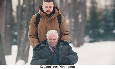 A young man walking outdoors with his grandfather in wheelchair at winter time