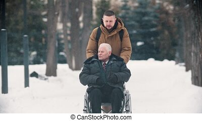 A young man walking outdoors with his grandfather in wheelchair