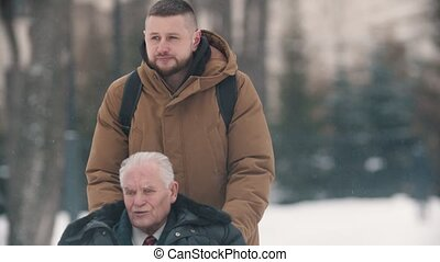 A young man walking outdoors with his grandfather in wheelchair under the snowfall