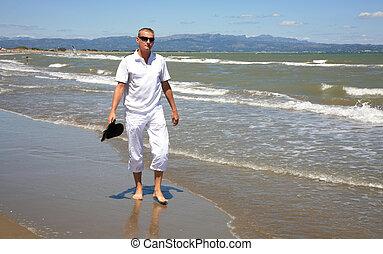 A young man walks along the Balearic Sea at Riumar beach in Spain