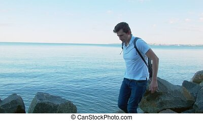 A young man walks along the big rocks by the sea.