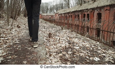A young man walks through the park in the spring or autumn trees yellow leaves, next to an abandoned German fort, brick walls, an old iron fence