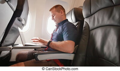 A young man was sitting on the plane and working on his laptop before departure.