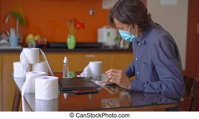 A young man wearing a face mask sitting at home during coronavirus self-isolation. He uses an alcohol sanitizer to disinfect everything that surrounds him. Slowmotion shot
