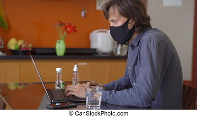 A young man wearing a face mask works from home during corona virus self isolation