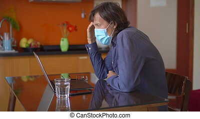A young man wearing a face mask works from home during coronavirus self-isolation. Camera reveals that he is in his underpants