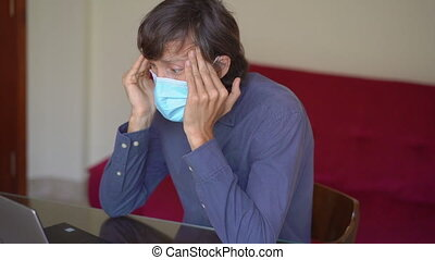 A young man wearing a face mask works from home during coronavirus self-isolation. He is very tired of staying at home and anxious about the future. Slowmotion shot