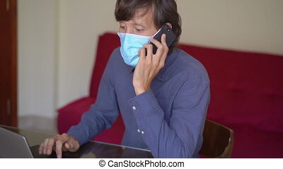 A young man wearing a face mask works from home during coronavirus self-isolation. He talks on a cell phone. Slowmotion shot.