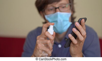 A young man wearing a face mask works from home during coronavirus self-isolation. He uses an alcohol sanitizer to disinfect his phone