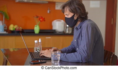 A young man wearing a face mask works from home during coronavirus self-isolation. Slowmotion shot