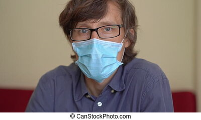 A young man wearing a face mask works sits at home during corona virus self isolation