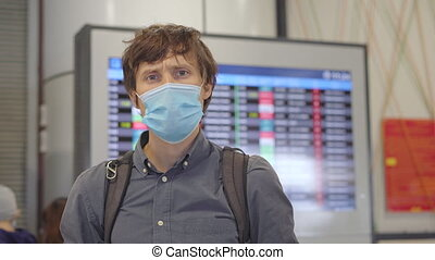 A young man wearing a medical face mask in an airport stands...
