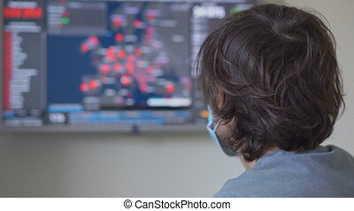 A young man wearing a medical face mask looking at the screen where the numbers of people infected with the covid-19 virus in Europe are shown. He is terrified by the data. Man turns back and looks at the camera