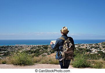 A young man with a backpack and a map of the area in his hands stands on a mountain near the city and the sea