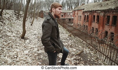 A young man With a beard, in a gray coat walks through the park in the spring or autumn trees yellow leaves, next to an abandoned German fort, brick walls, an old iron fence