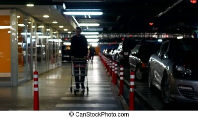 A young man with a cart goes on an underground car parking for shopping in a shopping center, concept