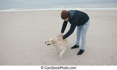 A young man with a dog meets his wife and daughter on the beach.