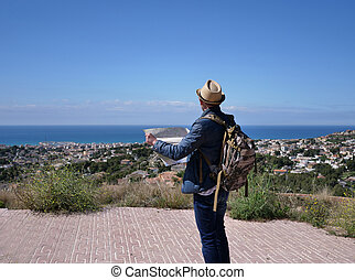 A young man with a map in his hands on the mountain looks at the village under the mountain