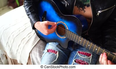 A young man with a tattoo on his chest plays the guitar in the bedroom. Hipster learn to play the guitar. Close-up of a man's hand playing a guitar string. Concept: rock musician