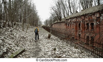 A young man With backpack on back walks through the park in the spring or autumn trees yellow leaves, next to an abandoned German fort, brick walls, an old iron fence