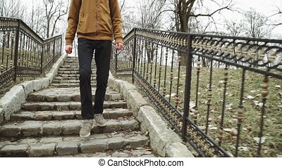 A young man With backpack on back walks through the park in the spring or autumn trees yellow leaves, Descends the steps