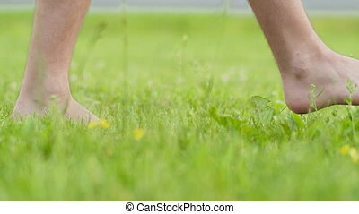 Young man with bare feet walking on the green grass. Healthy lifestyle