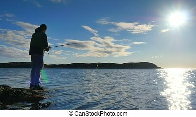 A young man with beard in black outdoor clothes is catching fish while standing on rocky shore. Bright sparkling water