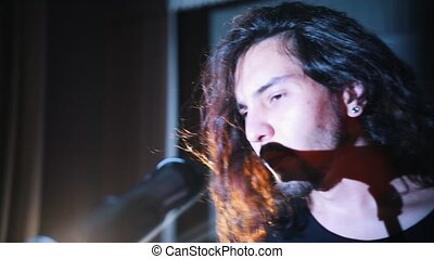 A young man with long hair walking to the mic on the stage and starts talking. Mid shot