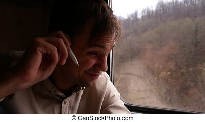 A young man with sensual lips thinks something against the background of the train window. 4k. Landscape, view of trees and forest from the window of a train on motion, nature.