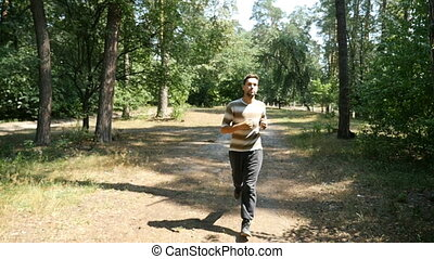 A young man with sportive figure in black pants runs in a forest in slow motion