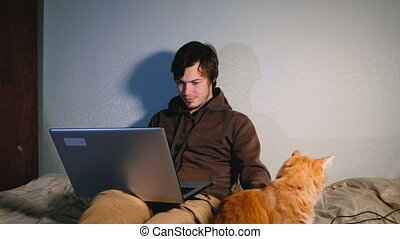 A young man working at the laptop on the bed with his cat,...