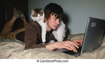 A young man working at the laptop on the bed with his cat, closeup.