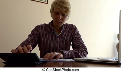 a Young Man Working With a Calculator And Calculating Something