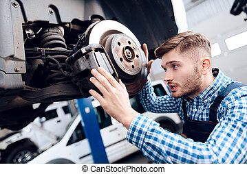 A young man works at a service station. The mechanic is engaged in repairing the car.