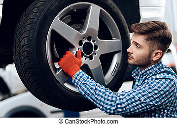 A young man works at a service station. The mechanic is engaged in repairing the car