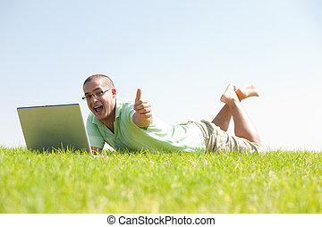 A young men sit on the in the park using a laptop
