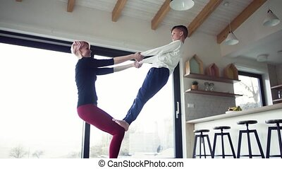 A young mother doing exercise with small son indoors at home.