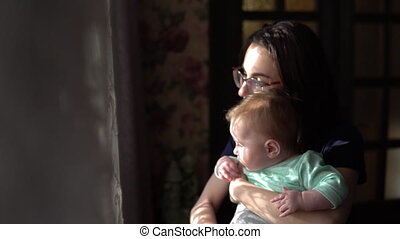 A young mother holds a baby in her arms. A woman with a child looking out the window.