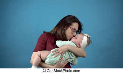 A young mother holds a baby in her arms. Woman with a daughter on a blue background. 4k