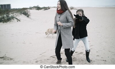 A young mother is dancing on the beach with her daughter.