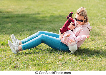 A young mother is sitting on the grass, playing with her baby. Recreation in the park with a child. Top view. Children's day